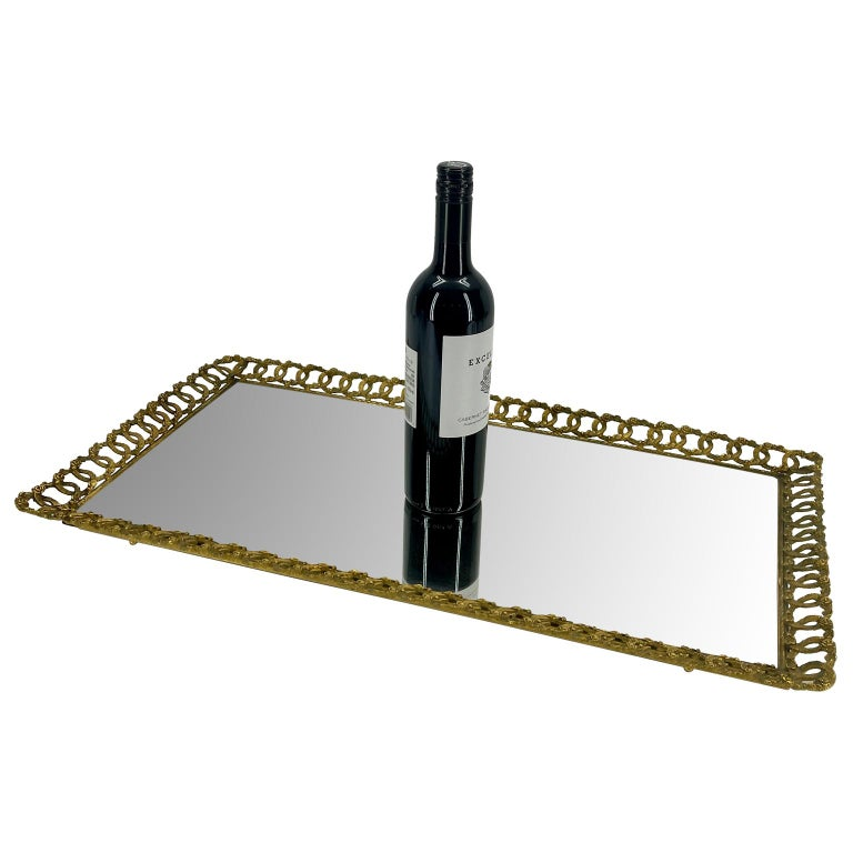 Hollywood Regency gilded serving or vanity tray. Large rectangular hand forged ornate tray with filigree link design. The interlocking circles topped with delicate floral design is beautifully elegant. The tray is sturdy and is as comfortable