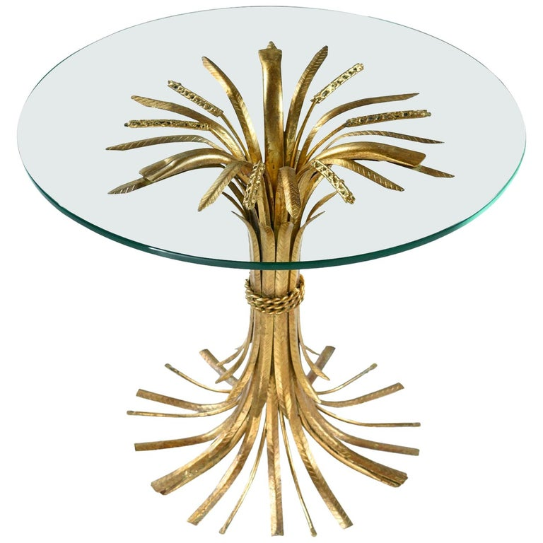 Elegant and luxurious, this Italian Hollywood Regency table glamorizes the humble wheat sheaf. The table is made of sculpted metal with a gold gilt finish and topped with a piece of circular glass. The circle glass top balances on top of the wheat