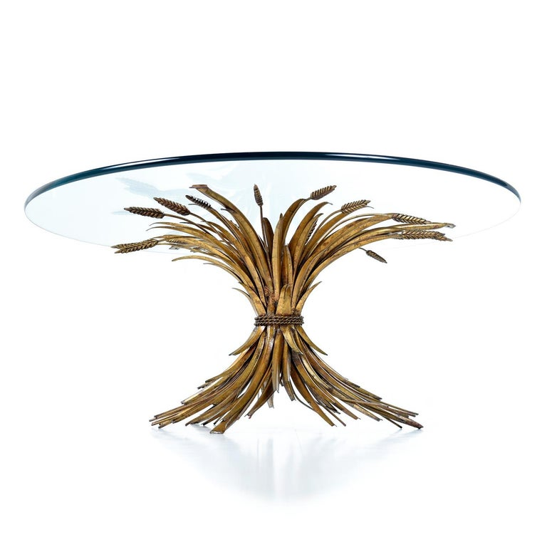 Elegant and luxurious, this Italian Hollywood Regency table glamorizes the humble wheat sheaf. The coffee table is made of sculpted metal with a gold gilt finish and topped with a piece of circular glass. The circle glass top balances on top of the