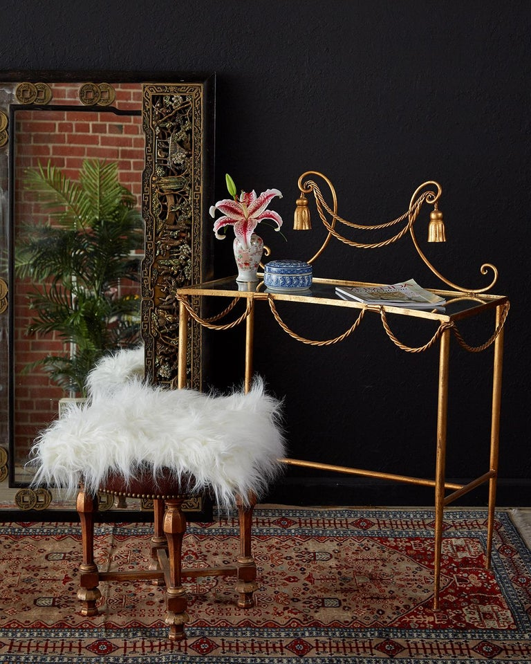 Diminutive gilt iron and faux rope vanity or console table made in the glamorous Hollywood Regency taste. Features a gilded iron frame decorated with iron rope swag and tassels. The top is scalloped with a glass insert and is supported by elegant