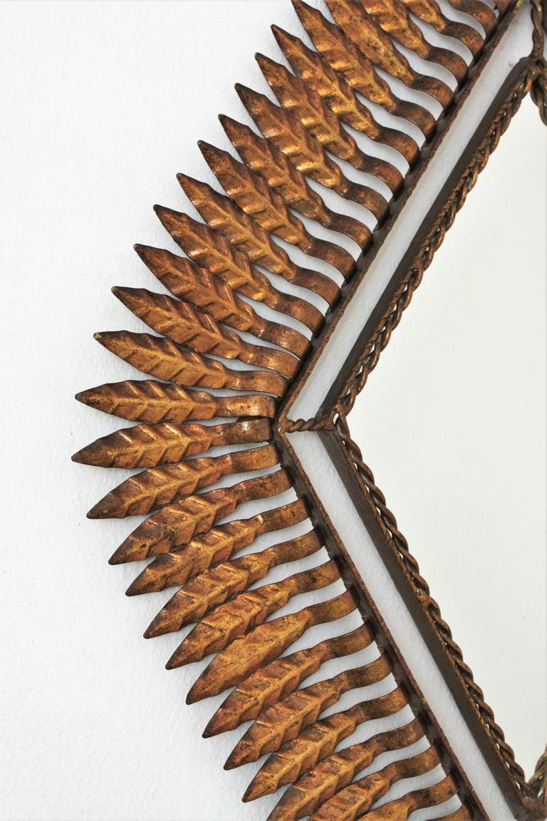 Hammered Hollywood Regency Gilt Iron Leafed Rhombus Sunburst Mirror, Spain, 1950s For Sale