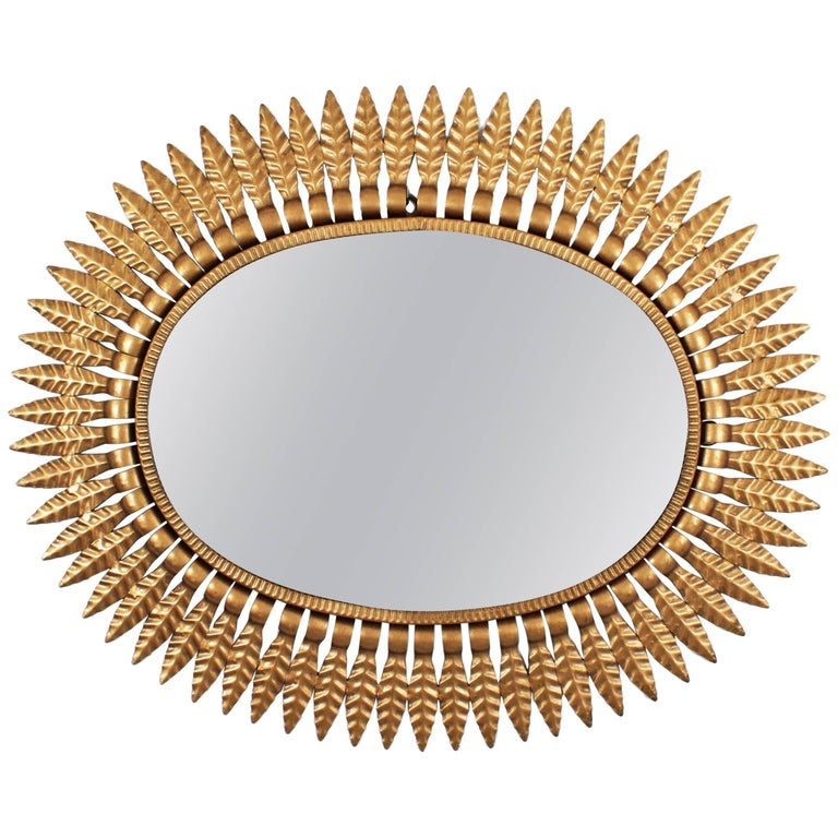 A Hollywood Regency style oval sunburst mirror framed with gilt metal leaves, Spain, 1950s.