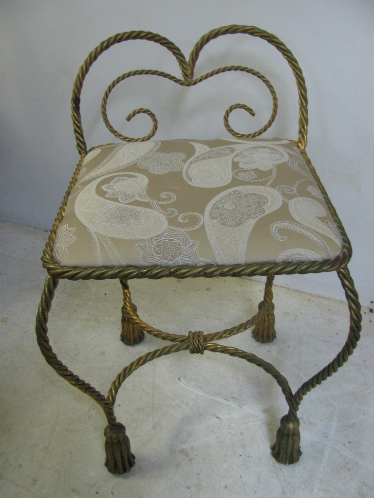 Fabulous gilt rope and tassel vanity seat. Recently upholstered but any easy switch if needed. Chair is sturdy and sits flat, will slide into and under most vanities.