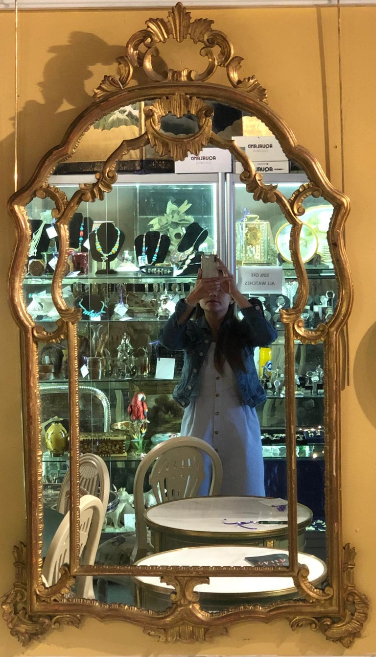 Hollywood Regency giltwood French shell carved wall or console mirrors. A Pair of spectacular finely scroll and shell carved wall, console or over the mantel (fireplace) mirrors. Each having a clean center mirror in a carved giltwood frame. The pair
