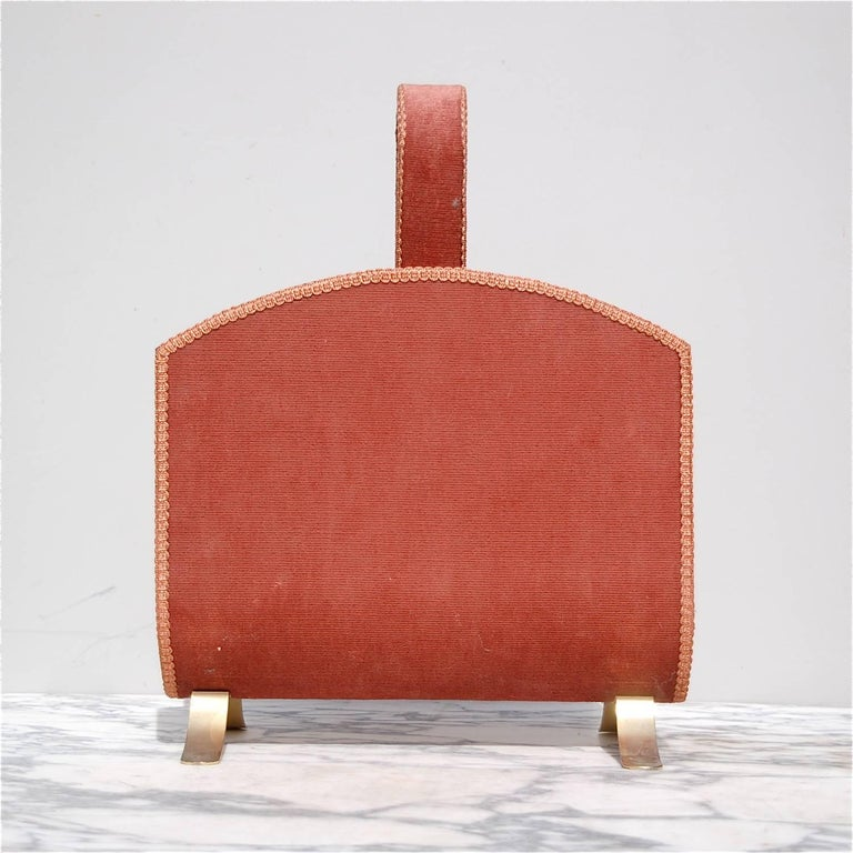 Mid-20th century magazine rack or newspaper holder in metal, which has been lacquered gold on the interior whilst the exterior is covered in its original dusty pink or vieux rose corduroy fabric with ribbon edging. Depending on which direction you