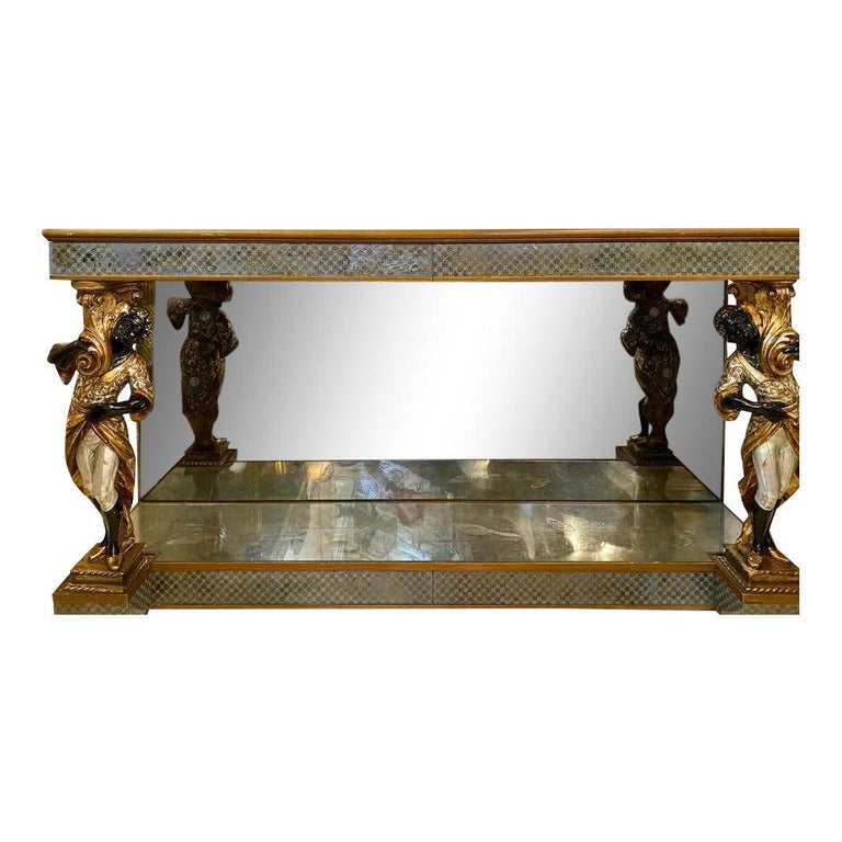 Hollywood Regency Maison Jansen figural and églomisé console table. This one of a kind simply stunning console table or sideboard has two drawers with églomisé fronts. The original mirrored tabletop is supported by a pair of magnificent flanking,