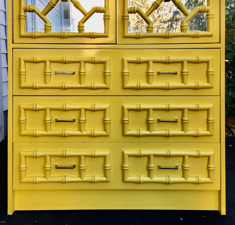 Mid-Century Modern Palm Regency faux bamboo mirrored storage armoire cabinet featuring a vibrant sunny yellow lacquered finish. This bright and happy Chinese Chippendale style cabinet has two mirrored front doors decorated with a dimensional bamboo