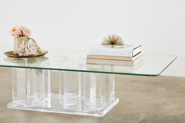 Fantastic Hollywood Regency coffee or cocktail table. Featuring a sculptural lucite base with facet cut stalagmite shape forms. The large rectangular pane of glass rests upon a bed of angular shapes that reflect and play with the reflections of
