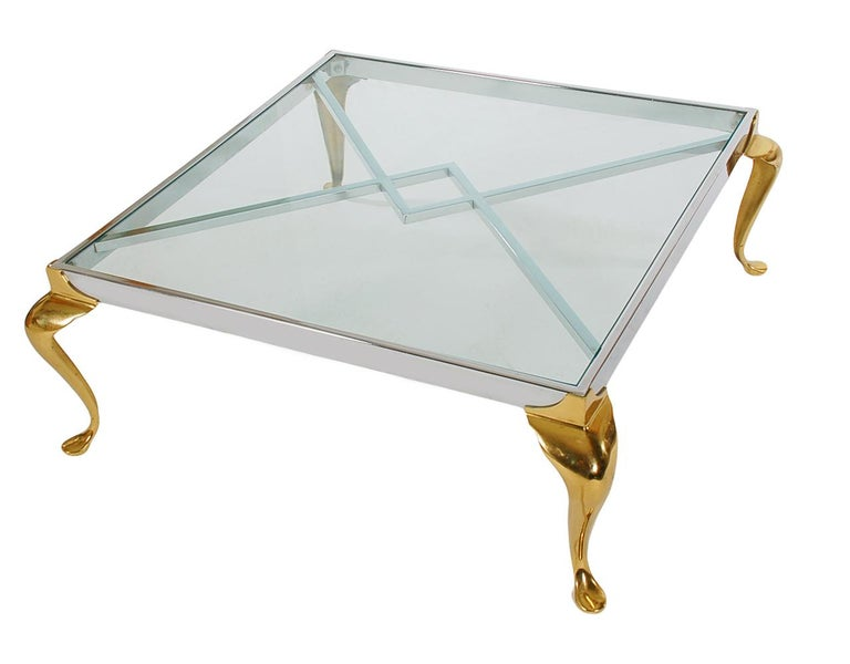 A handsome looking two-tone transitional design cocktail table, circa 1970s. It features brass and chrome construction with inlayed glass top.