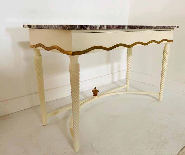 Hollywood Regency marble-top console. Console is wood with a white lacquered finish. Has a pull-out drawer with gold trim and a gold finial.
