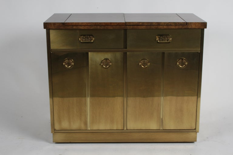 Beautiful 1970s Mastercraft dry bar, cart or server with warm factory applied patina to the brass cladded cabinet and elm burl veneer flip top for extra serving space. Drawers and doors have Asian inspired hardware, lower cabinet has two doors that