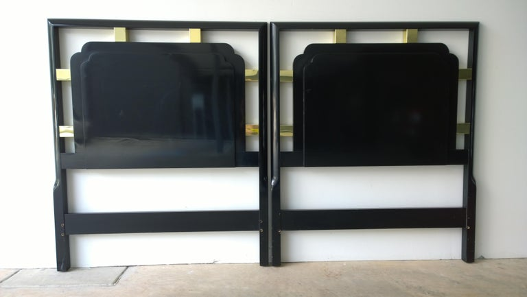 Offered is a pair of Hollywood glam or Mid-Century Modern twin (together a king) headboards that are lacquered in a high sheen black with gilded metal accents that complete a Hollywood Regency look. Would also look great lacquered in white, navy,