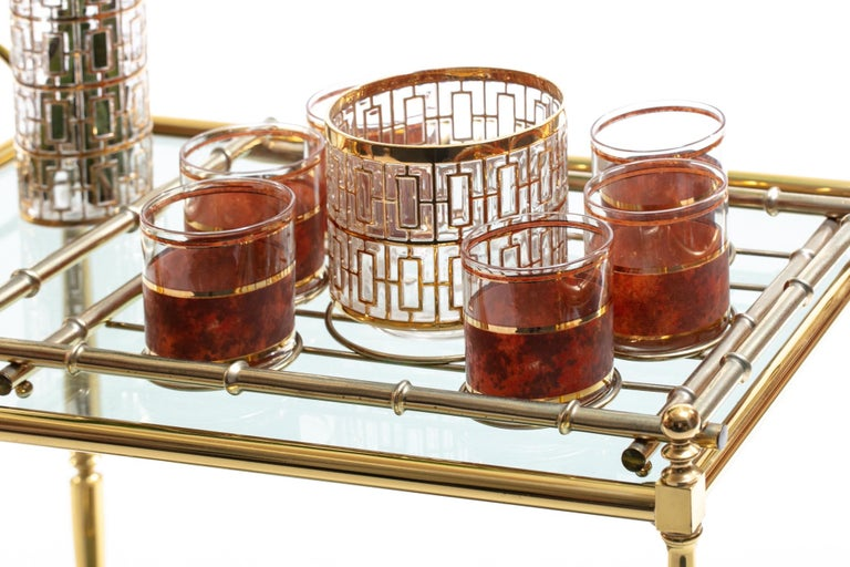 Beautiful and elegant mixed Hollywood Regency Mid-Century Modern barware set featuring 22-karat gold hand painted ice bucket by Imperial Glass in the famed Shoji pattern, six rocks glasses with 22-karat gold plated detail and faux suede finish, and