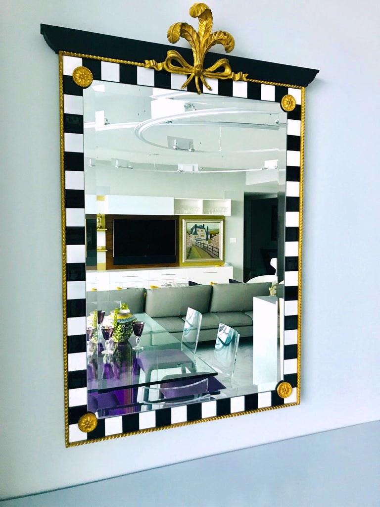 Elegant Hollywood Regency mirror with neoclassical design. Mirror features exquisite ornamentations throughout. Carved wood plumes in hand laid antique gold leaf adorn the top over an ebonized wood pediment. The mirror features contrasting black and