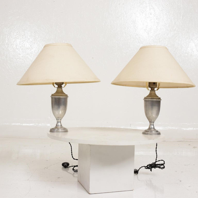 For your consideration, Hollywood Regency pair of petite table lamps in aluminum.  Made in the USA circa 1960s. Unmarked. Constructed in aluminum. No lampshades included. Rewired.   Dimensions: 9 1/2