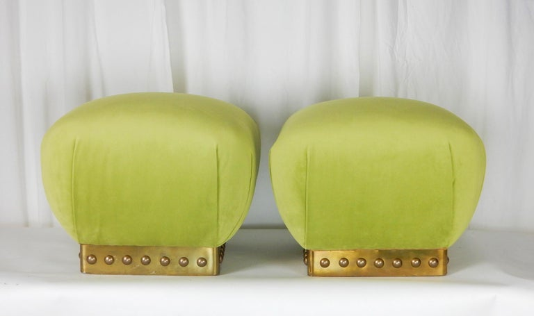 Pair of absolutely divine vintage 1970s Pouf ottomans that were just newly upholstered in soft plush green velvet. Brass trimmed bases embellished with large bronze half round dome tacks. These make perfect extra seating in a living room or