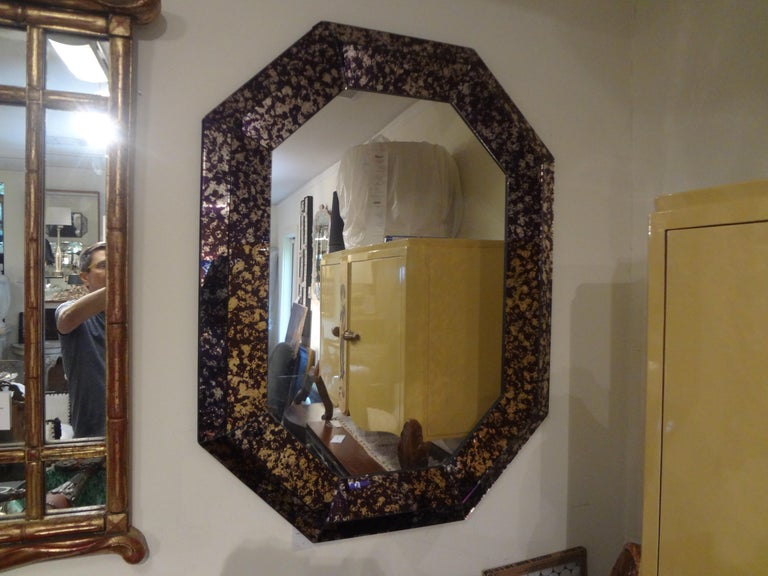 Stunning and unusual Hollywood Regency purple octagonal mirror. This beautiful midcentury mirror has a purple and silver geometric cushion perimeter surrounding a silver plate central mirror. Can be displayed vertically or horizontally.