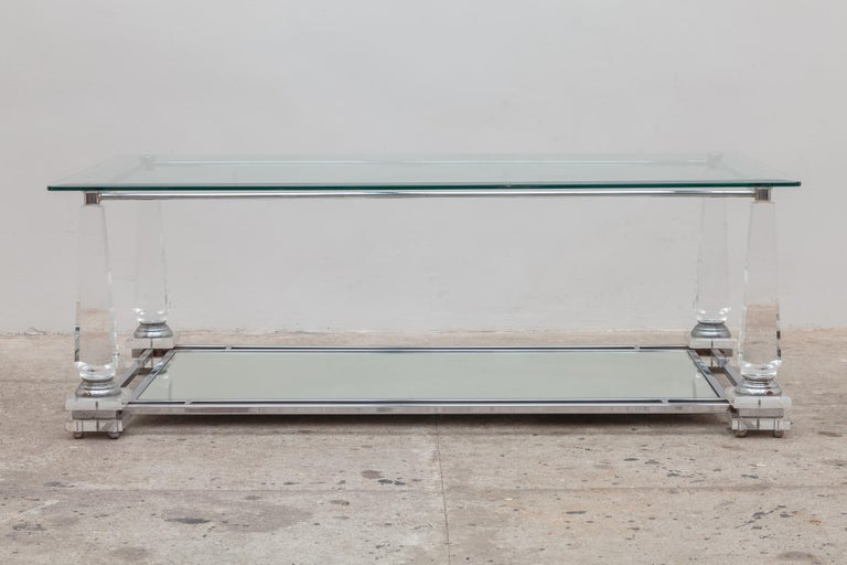 Vintage 1970s rectangular coffee table. Crystal Lucite obelisk legs support a lower mirrored shelf and a top shelf of clear beveled glass.Top of the table resting on the 4 obelisk legs which are magnificent well stabile and solid. Measurements: Dept