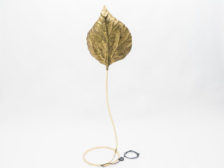 This iconic single leaf Rhubarb floor lamp by Tommaso Barbi was produced by Carlo Giorgi in Italy in the 1970s. The circular brass frame sweeps upwards from the base to support the large, decorative, hammered brass leaf. The handcrafted element
