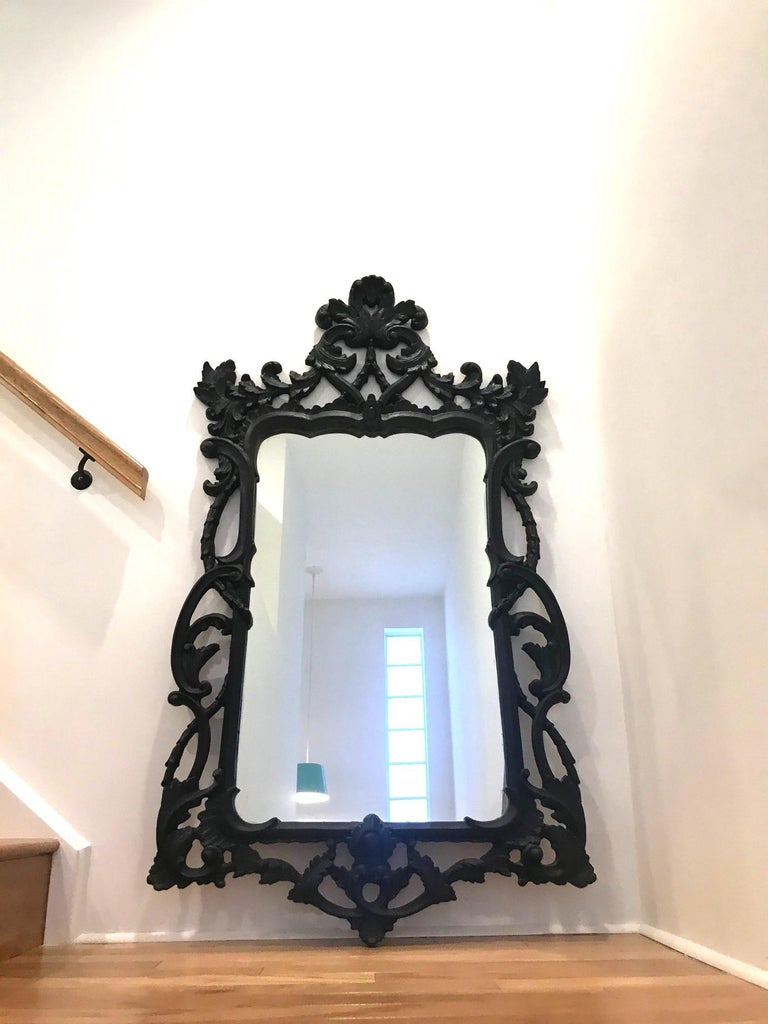 Large Hollywood Regency mirror with traditional Rococo style carved wood frame. Mirror has shield design featuring a series of hand carved scrolls with foliage details. The vintage black finish has a slightly distressed quality which gives the