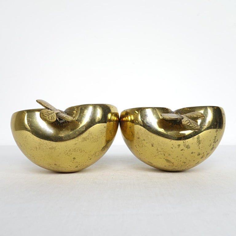Attractive set of two shiny brass apple parts that make perfect bookends due to their impressive weight as they are filled with sand. Marked