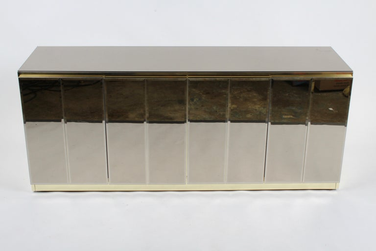 Fabulous Hollywood Regency signed Ello sideboard /buffet with bronze mirror top, bronze beveled glass doors and brass detailing. The interior having adjustable shelving and a single drawer. Shelves are 35