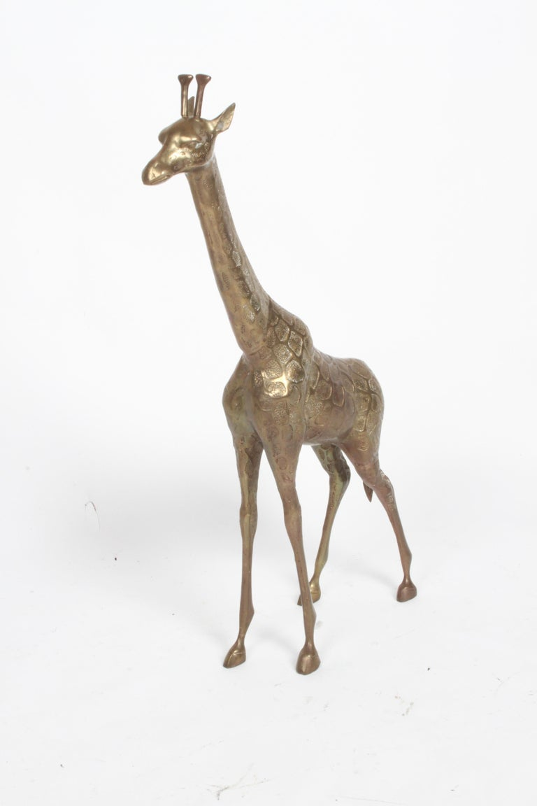 Vintage Hollywood Regency style standing brass Giraffe floor statue or sculpture circa 1970s. Original patina, unpolished. In fine condition, no damage noted.