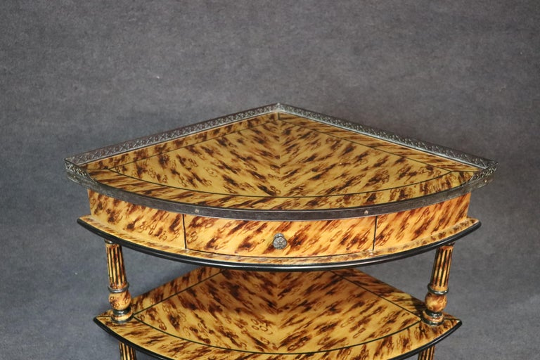French Hollywood Regency style tortoise painted corner étagère with a brass gallery.