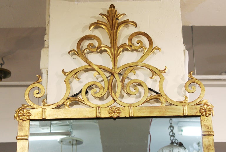 Hollywood Regency style wall mirror in gilt metal with scrollwork crest