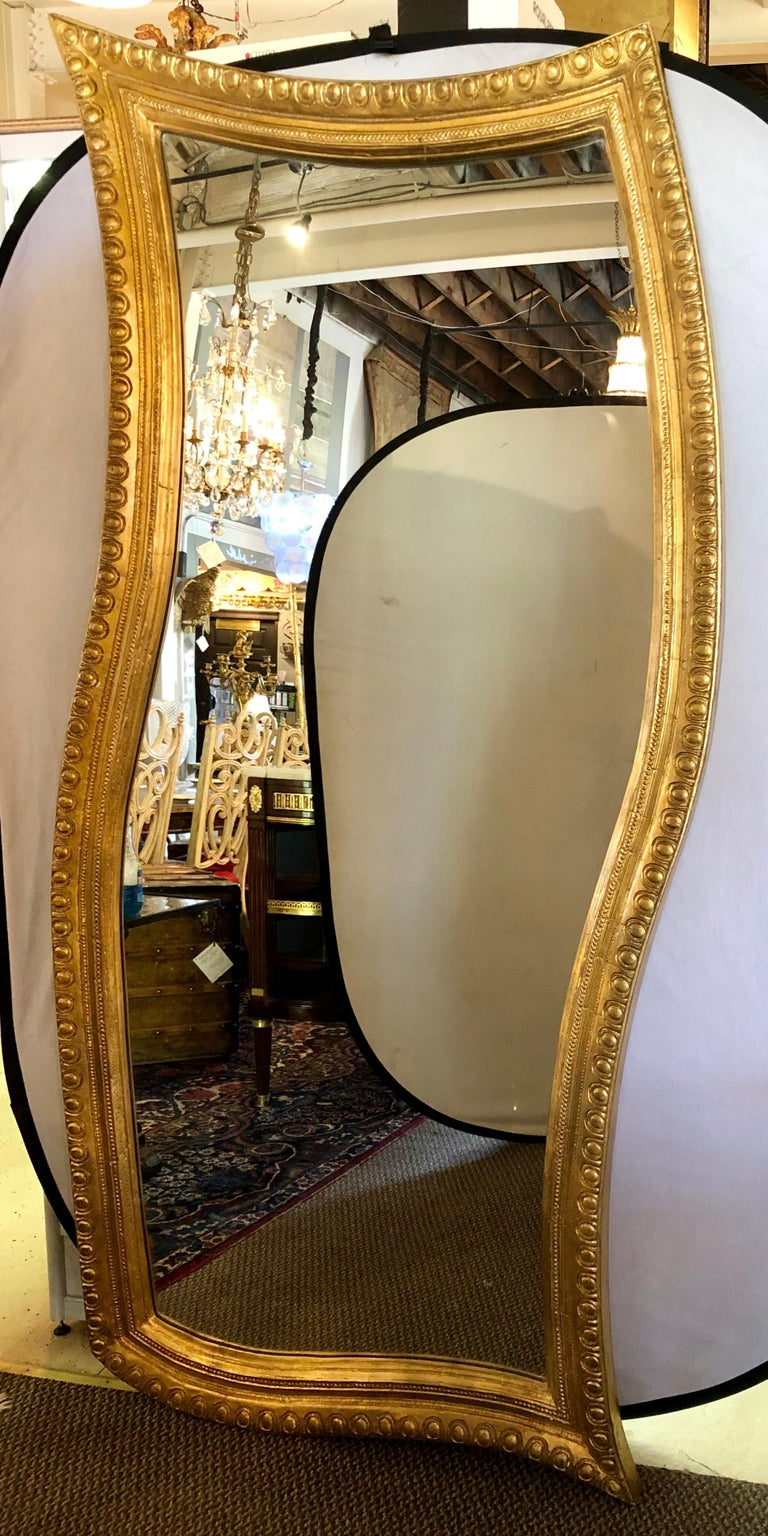 Hollywood Regency style giltwood carved standing floor or wall mirror. This finely carved and decorative mirror can hang vertically or horizontally.