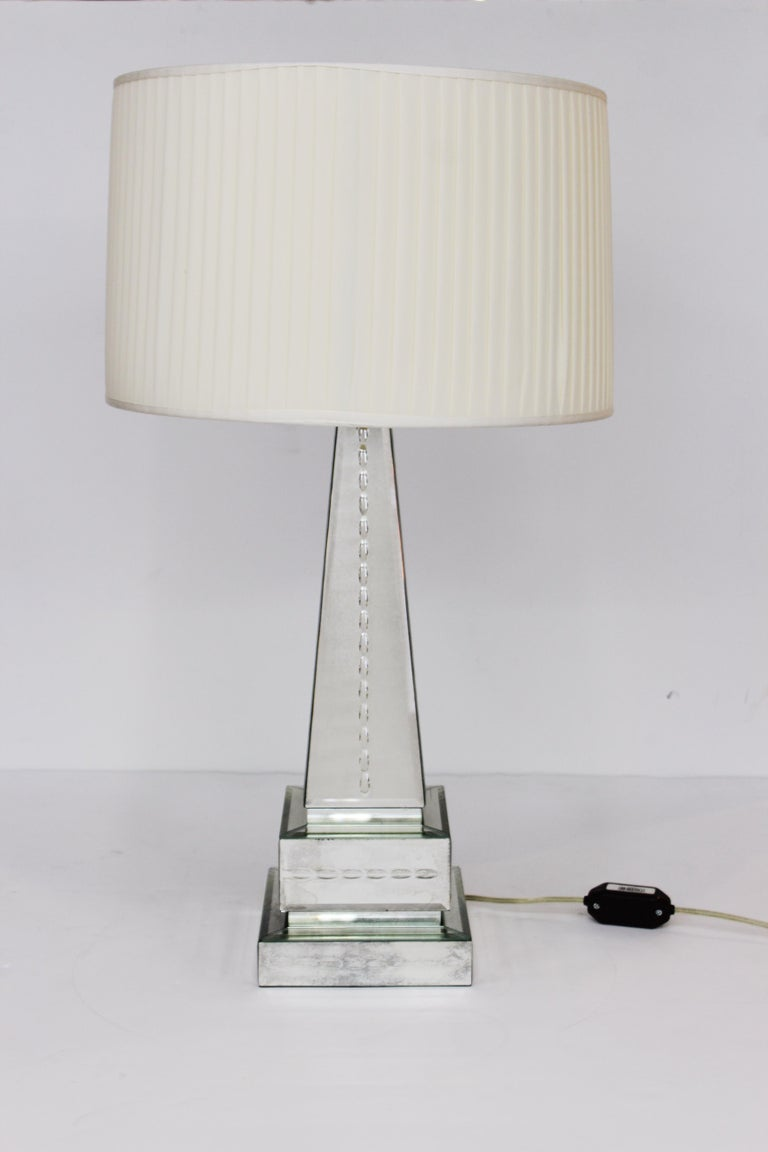 Hollywood Regency style pair of mirrored obelisk table lamps on mirrored bases, with shades. The pair is in great vintage condition with age-appropriate wear to the mirrored surfaces. The shades measure 10.5 in. height x 16 in. diameter.