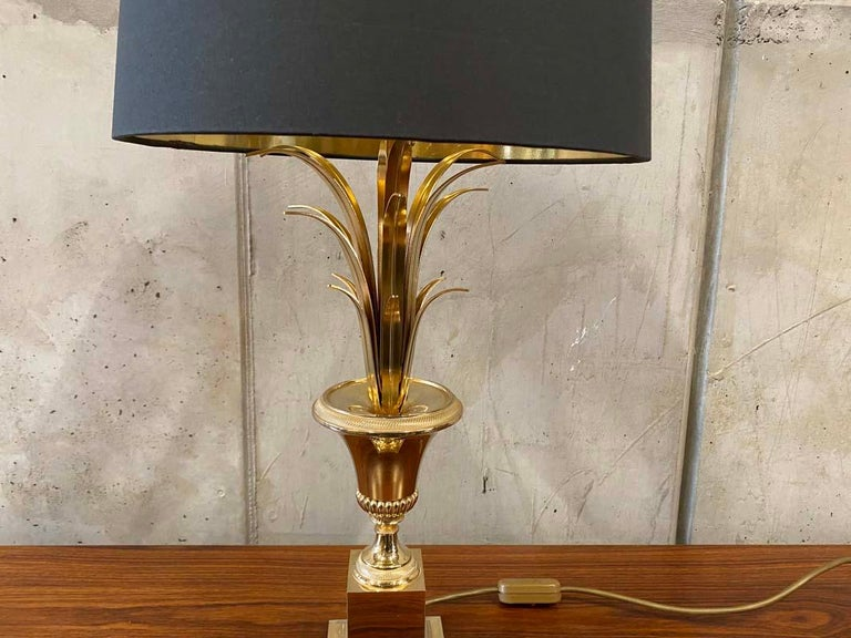 I would attribute this particular Hollywood Regency style table lamp to Maison Jansen. It stands on a gilded base in the shape of a palm tree and must be from the 1970s. The new lampshade is made of linen in anthracite and shiny gold from the inside