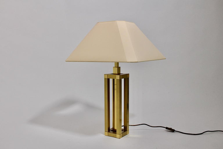 Hollywood Regency style vintage table lamp from brass, which design is very similar to Romeo Rega design Italy 1970s. While the table lamp base shows a brass construction in geometric shape, the renewed lamp shade shows an ivory color tone. The