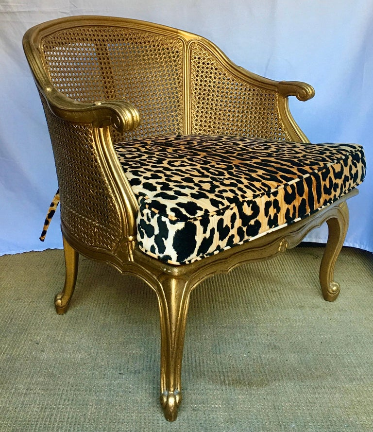 Hollywood Regency style arm accent chair with gilt painted frame, curved cabriolet legs, and cane back/sides. Back and sides of chair are double caned. New insert custom upholstered in a leopard animal print velvet. Chair labeled