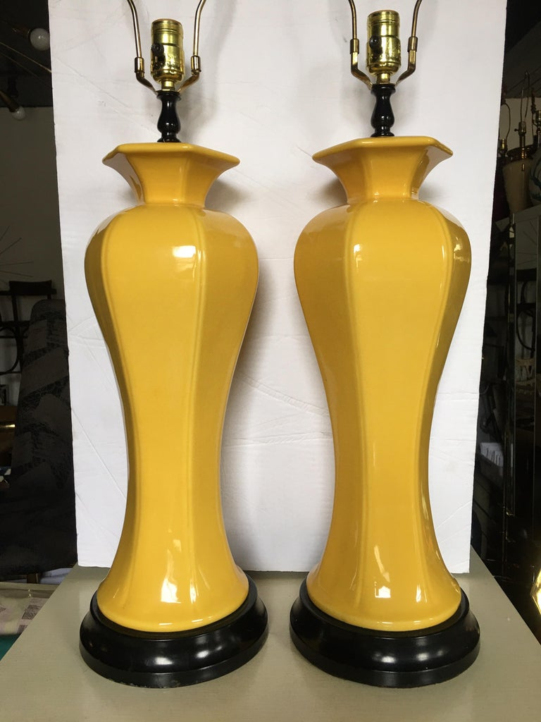 Sculptural Pair of Hollywood Regency Chinoiserie tall sunny yellow ceramic glazed table lamps mounted on black plinth bases.   Measures: Height to finial 33 inches. Height to socket 25.5 inches.