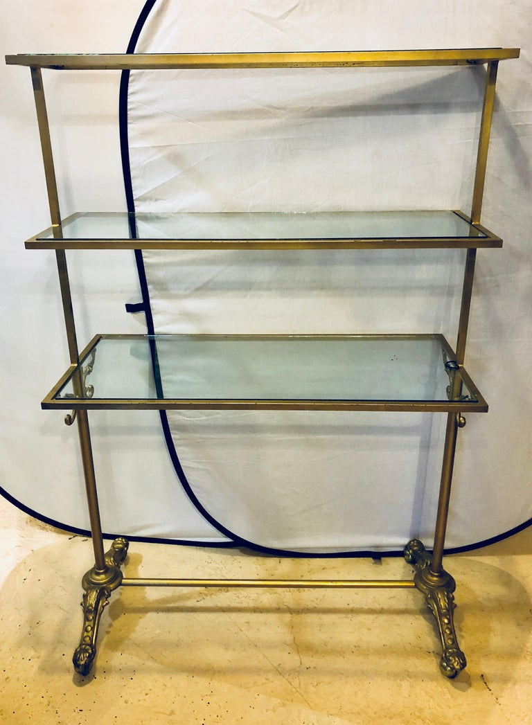 A Hollywood Regency three-tier large bakers rack gilt metal and glass shelves. A large and impressive bakers rack that is certain to add years of style and grace as well as serving a purpose to any kitchen or dining serving room in the home. 