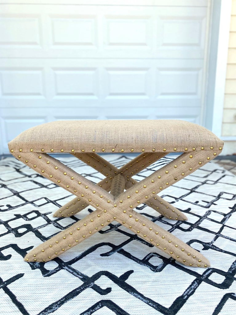 Hollywood Regency style bench with stylized X - Base frame. Completely upholstered in organic jute fiber burlap fabric with gold nail studs throughout. Makes a chic accent bench for any room.