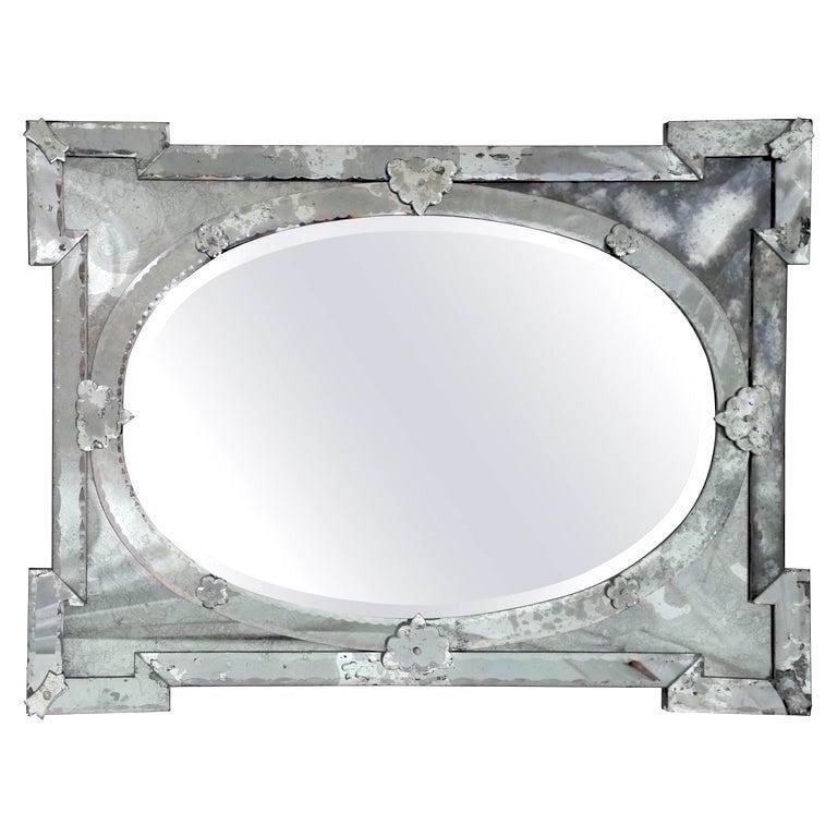 Exquisite large scale Venetian mirror with beveled edges and beautiful hand etched designs throughout. The mirror features a stunning oval center within a shield shaped frame with Smokey glass. Stunning Hollywood Regency Art Deco Era design, mixing