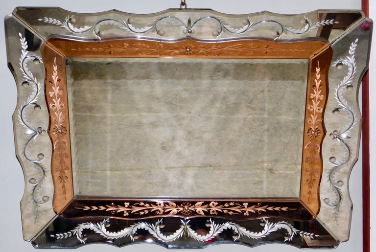 Elegant Venetian, circa 1940 Hollywood Regency mirror with reverse plume and starburst etched panels. The inner panels are a lovely peach color with delicate reverse etched design. The whole mirror is in very good condition retaining all the
