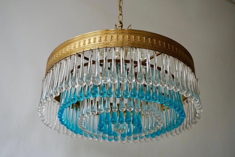 An elegant flushmount chandelier with blue and transparent crystal teardrop glass segments in a radial pattern. The result is a very sparkling effect typical of Hollywood style and glamour. The fixture is brass and the glass is hand blown.