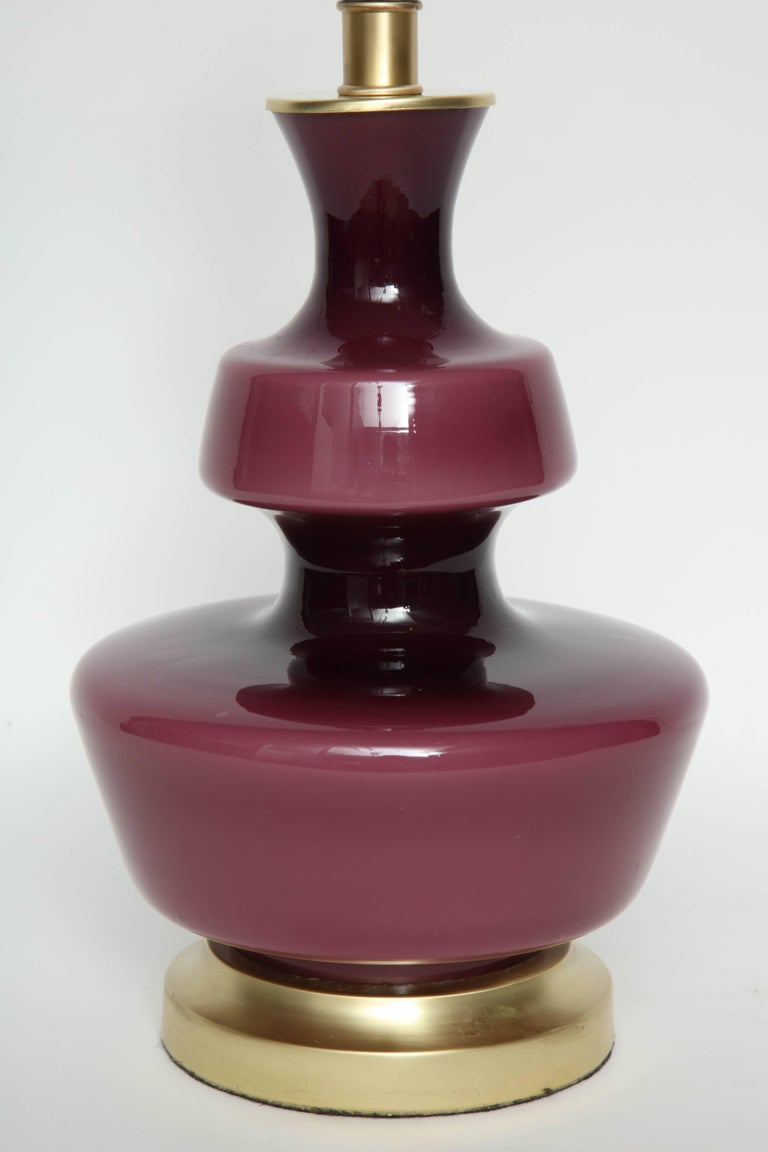 Pair of Scandinavian Modern pawn shaped raspberry colored glass lamps on satin brass bases by Holmegaard of Sweden. Rewired for use in the USA.  Glass portion measures 12.25