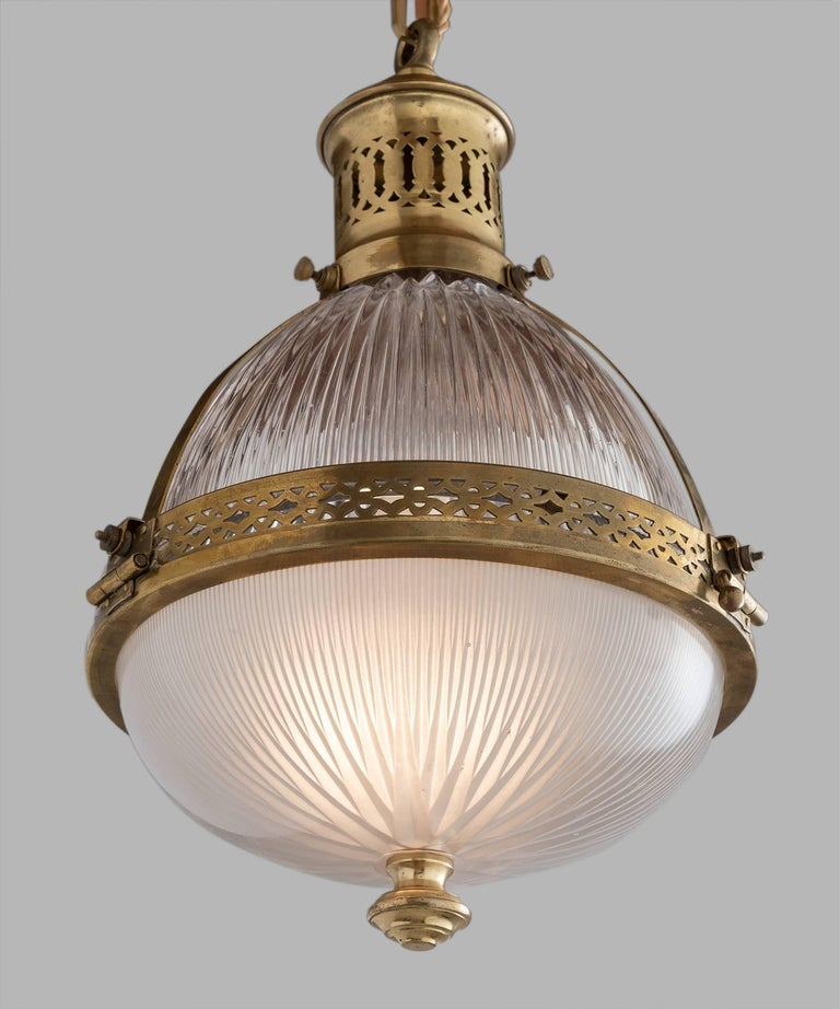 Holophane brass pendant, France, circa 1930.  Two-part prismatic holophane shade with brass hardware. Height includes chain.  Measures: 10.25