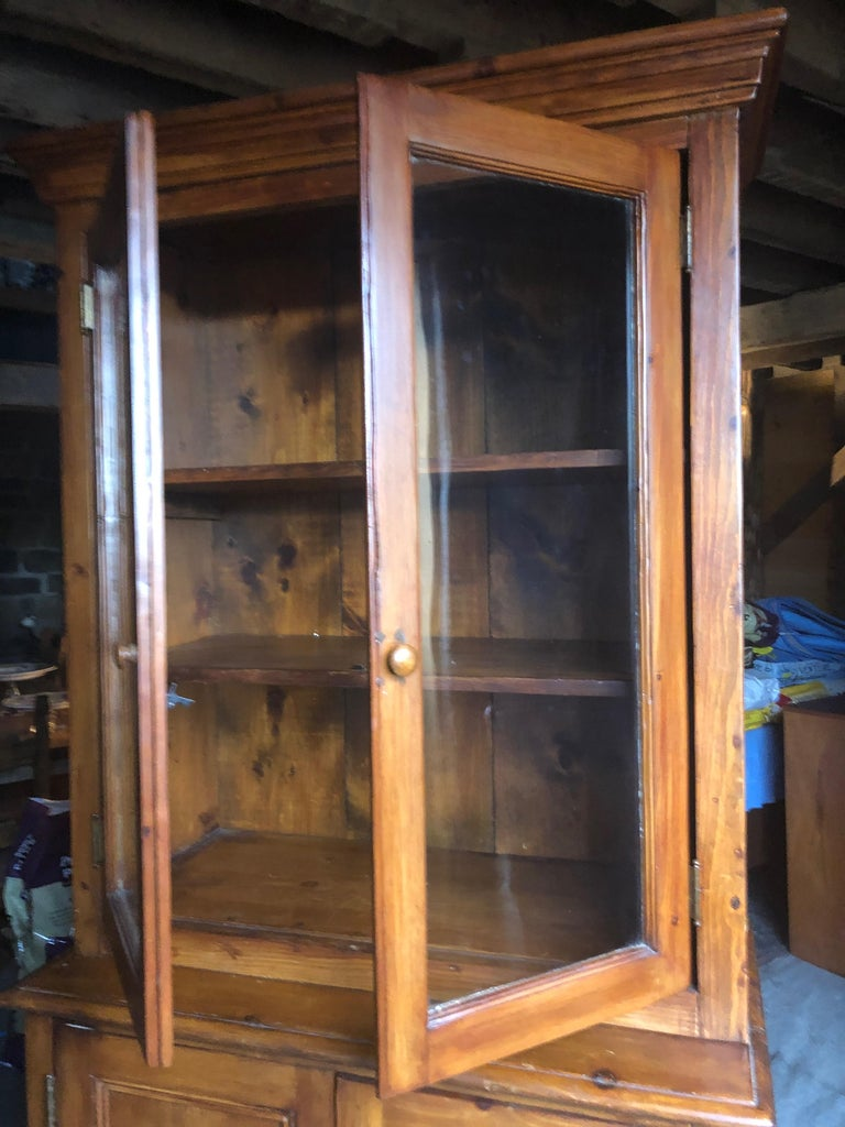 A warm and charming country cupboard cabinet having two glass doors on the top section and handsome stepped cornice, original glass and shelves inside. The bottom section has two wooden doors that open to more interior storage. 39.25 W bottom part