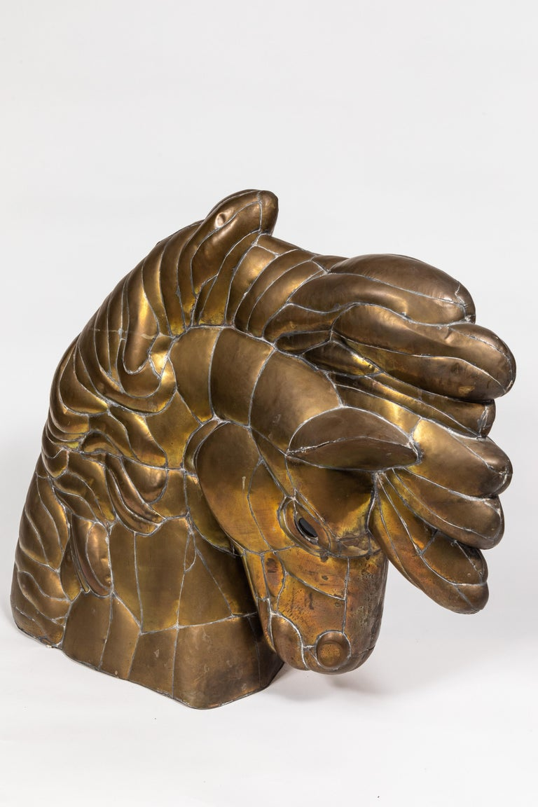 This expressive horse head sculpture in pieced and welded brass features flared nostrils, a flowing mane, and glass eyes. It rests on its finished and closed base. Hollow. No signature found.