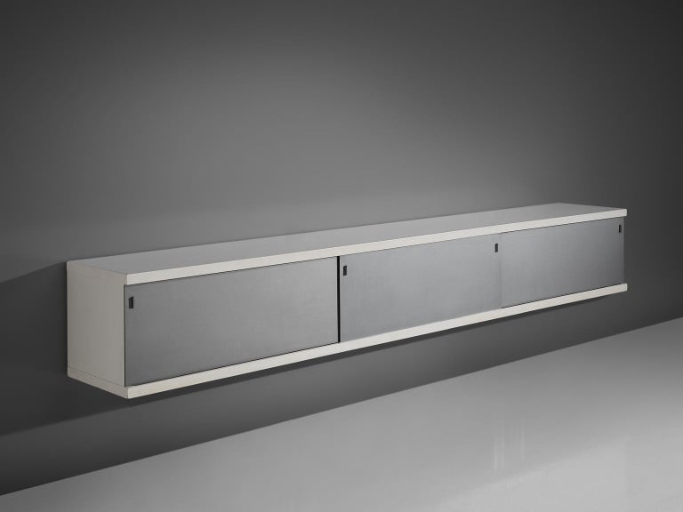 Horst Brüning for Behr, credenza, off white plywood and aluminum, Germany, 1960.  This simplistic geometric credenza holds a off white plywood frame and a brushed metal frame. The sliding doors are made of aluminum and have geometric grips. The