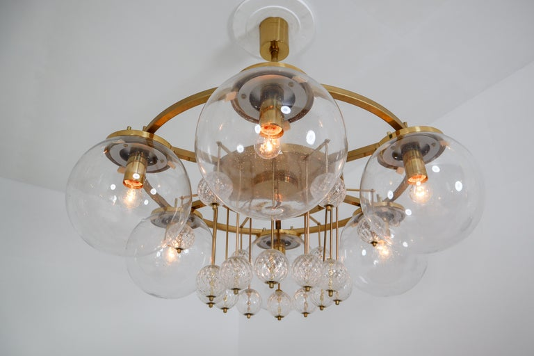 Large hotel chandelier with brass fixture and large handblown glass. The chandelier with brass frame consist of six lights, formed in a circle, with glass shades. The pleasant light it spreads is very atmospheric. Completed with the structured glass