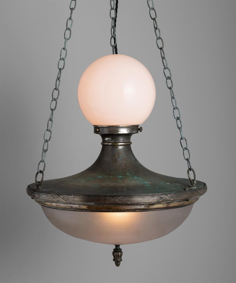 Opaline and frosted glass shades, with ornate patinated brass body.