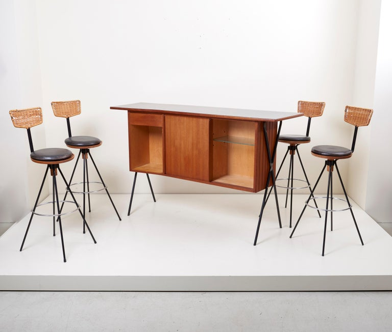 A house bar and four bar stools, designed by Prof. Herta-Maria Witzemann for a villa near Tübingen (Germany), manufactured by Erwin Behr, Germany, teak construction on four legs, black coated metal base, the bar stools with woven cane backrests,