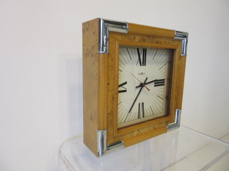 A maple burl wood framed wall clock with cast chrome accents to each corner and a cream face with roman numeral numbers. Battery operated and hanging hole drilled to the backside with paper information certificate from the manufacture Howard Miller