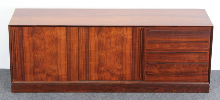 A beautiful H.P. Hansen rosewood credenza manufactured by Mobelindustri Randers in Denmark. Very versatile with five drawers and two sliding doors with two interior shelves. The sideboard is in very good condition with age appropriate wear.